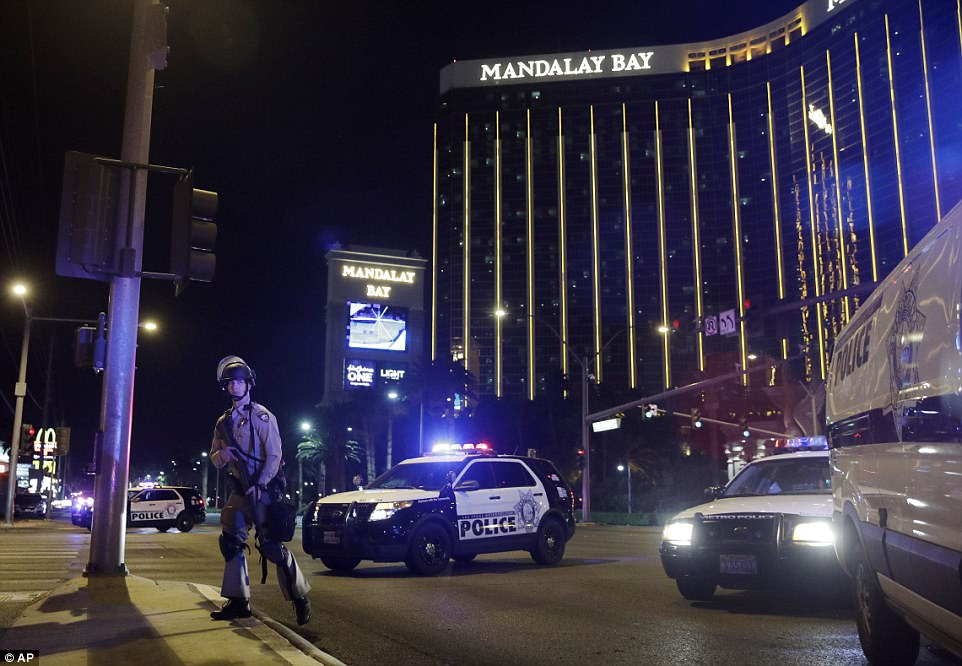 Police officers stand along the Las Vegas Strip the Mandalay Bay resort and casino during a shooting near the casino, Sunday, Oct. 1, 2017, in Las Vegas