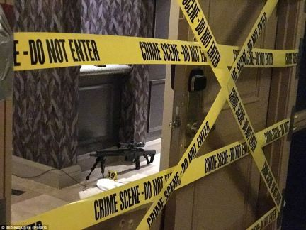 On the ground behind the double doors, one of Paddock's 23 firearms is seen set up on the ground with a bipod