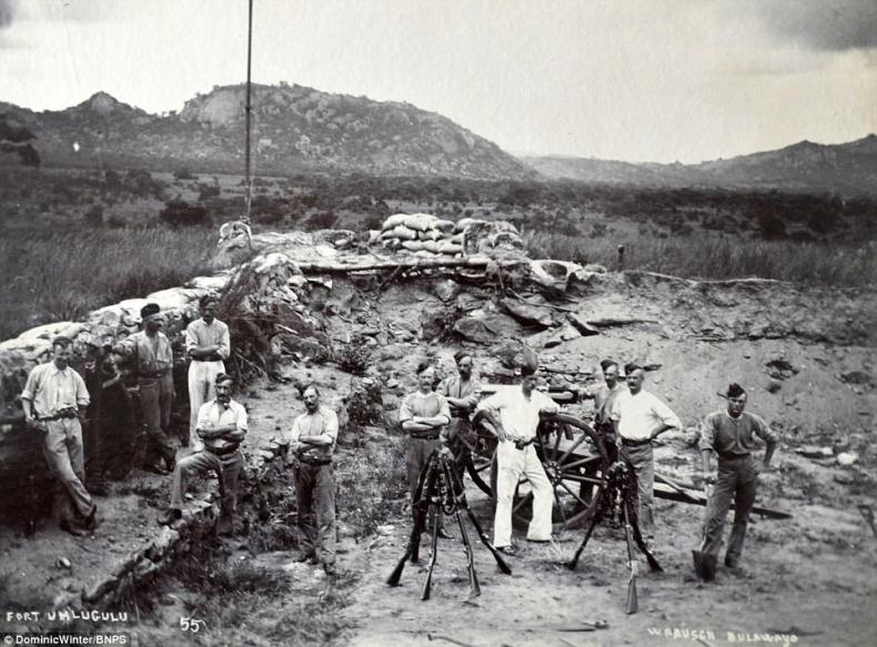 This image shows military men hard at work with their sleeves rolled up posing in front of their weaponry at Fort Umluglu, Bulawayo