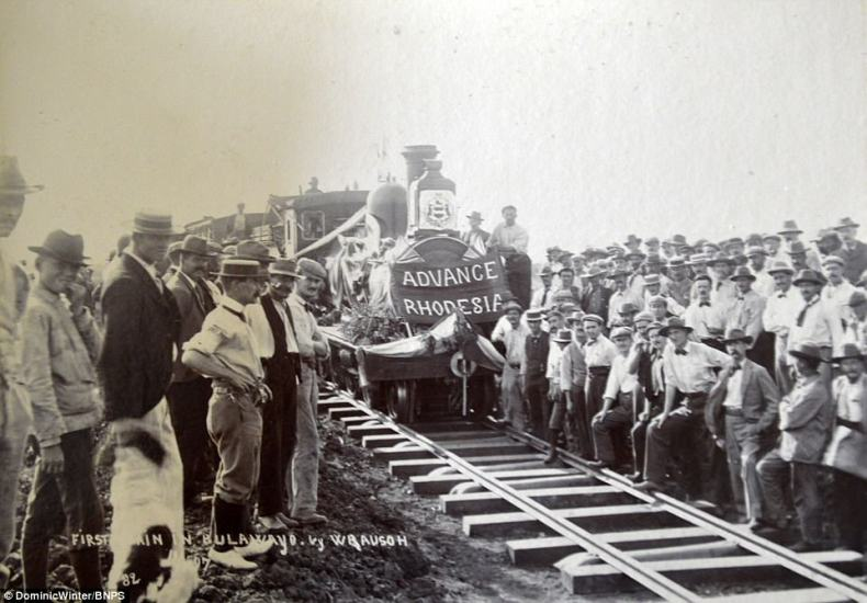 This photograph shows the first train coming intoBulawayo. A banner on the front of the train says: 'Advance Rhodesia'