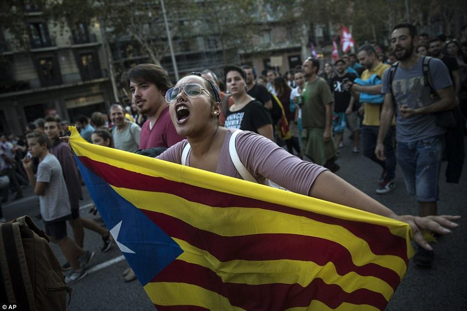 Una mujer lleva una bandera de la independencia catalana durante una marcha de manifestación en Barcelona ayer contra la confiscación de urnas y cargos sobre civiles desarmados durante el referéndum del domingo