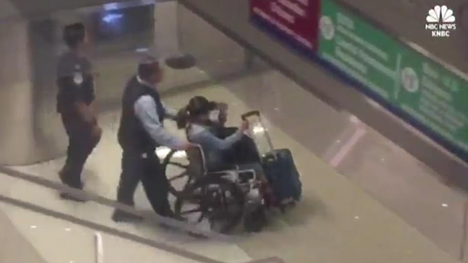 Back in the US: Marilou, 62, was seen in a wheelchair while clutching a suitcase and shielding her face with a visor. It is unclear why she was in a wheelchair