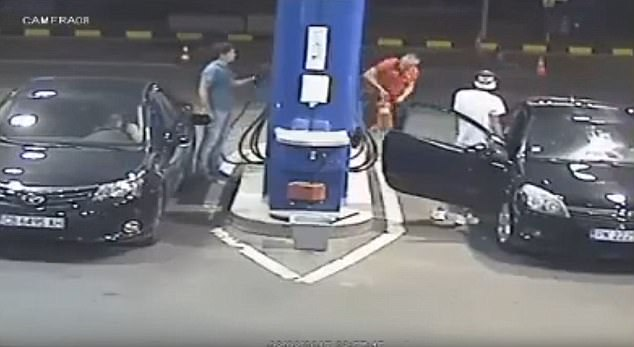 A man in a red shirt then appears towards the rear of the pump and dislodges a fire extinguisher