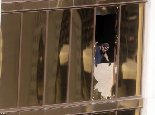 An investigator is seen on Wednesday peering through one of the windows that Paddock smashed so he could open fire on the crowd.  Lombardo also revised the number of injured down from 527 to 489, citing hospital confusion during the shooting