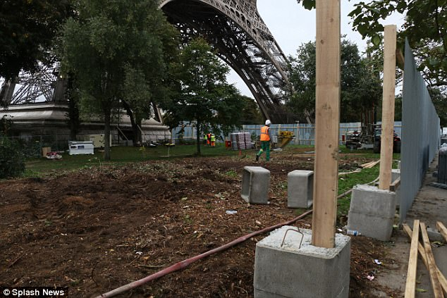 Workmen are pictured constructing Eiffel Tower's bullet proof glass wall in Paris, France today as an investigation continues into a truck found with a 'crude' detonation device underneath