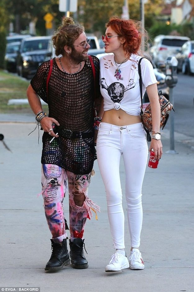Happy couple! Her new make out buddy wore a black mesh shirt over his tattooed torso and multi-colored distressed jeans with graffiti work splattered across his legs