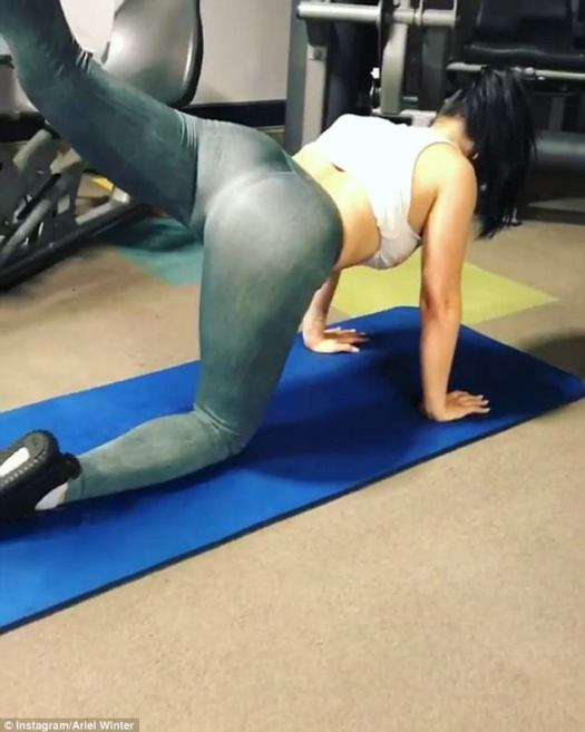 'Working on the (apple emoji)': Kneeling down on the yoga mat, she performed a rear leg lift to the camera, building up her toned derriere