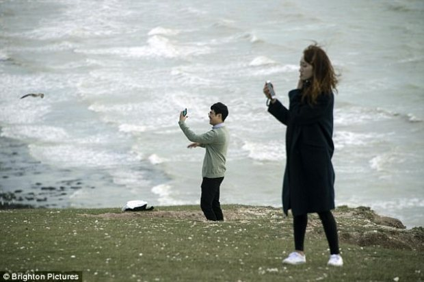 The site in East Sussex has become a hot-spot for thrill seekers and despite numerous signs warning of the dangers, tourists regularly teeter on the edge for photographs. Above, people taking risky selfies today at the cliffs