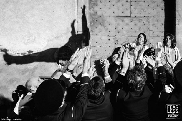 Crowd surfing:A bride watches as a man, presumably her groom, leaps into the outstretched hands of their wedding guests in this image taken by William Lambelete of southern France
