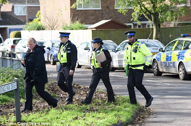 Police officers near the scene in Fordingbridge, Hampshire, conduct house to house enquiries
