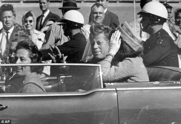 President John F. Kennedy waves from his car in a motorcade approximately one minute before he was shot in Dallas (Pictured: Nov. 22, 1963)