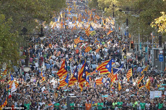 Protesters wave Catalan independence flags as they demonstrate against the Spanish federal government's move to suspend Catalonian autonomy