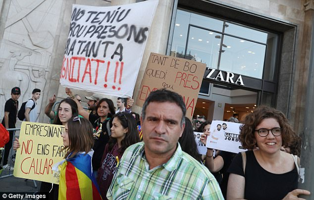 Protesters carrying signs to demand the release of imprisoned Catalan leaders Jordi Sanchez and Jordi Cuixart walk past a Zara clothing