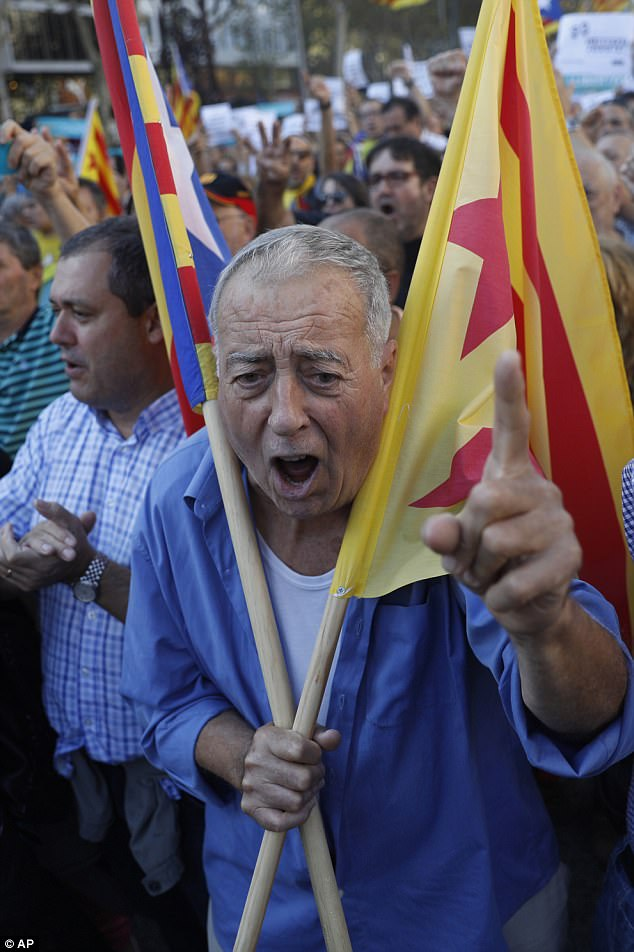 A protester carrying an ''estelada'' or Catalonia independence flag shouts during a march to protest against the National Court's decision to imprison civil society leaders
