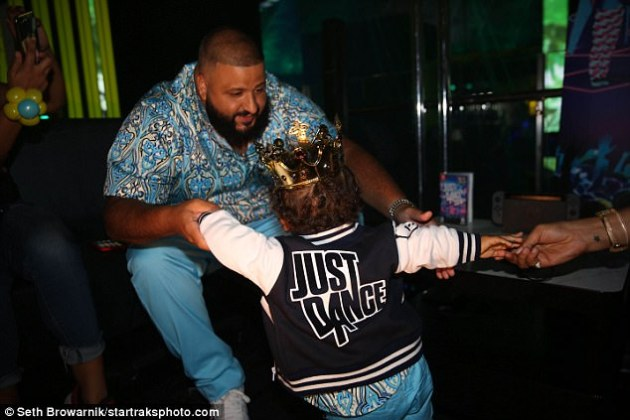 So sweet: As the party rumbled on, Asahd found himself bundled up in a bomber jacket that read 'JUST DANCE' on the back