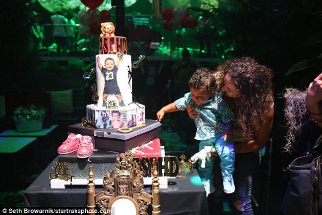 Doting mom: She also lowered him so he could have a look at his birthday cake