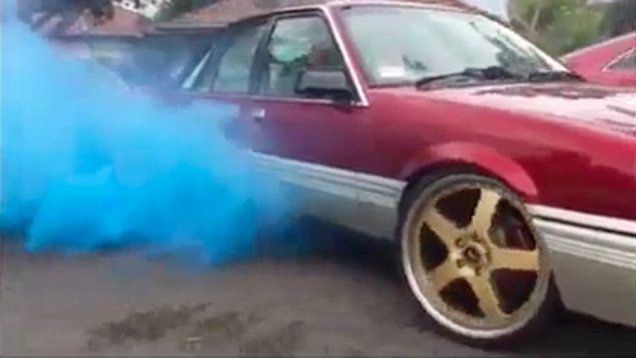 pregnant couple use coloured car exhaust smoke for gender reveal