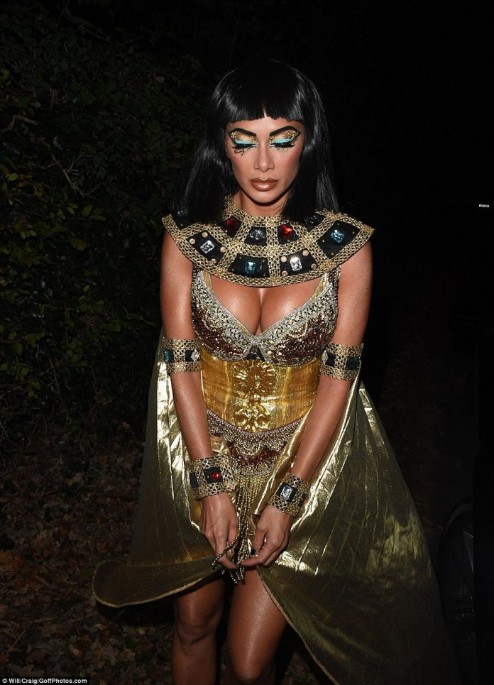 Sizzling: The glamorous goddess rocked the incredible gold look, which showed off both her amazing cleavage and her taut legs, and the metallic detailing on the look certainly made it stand out
