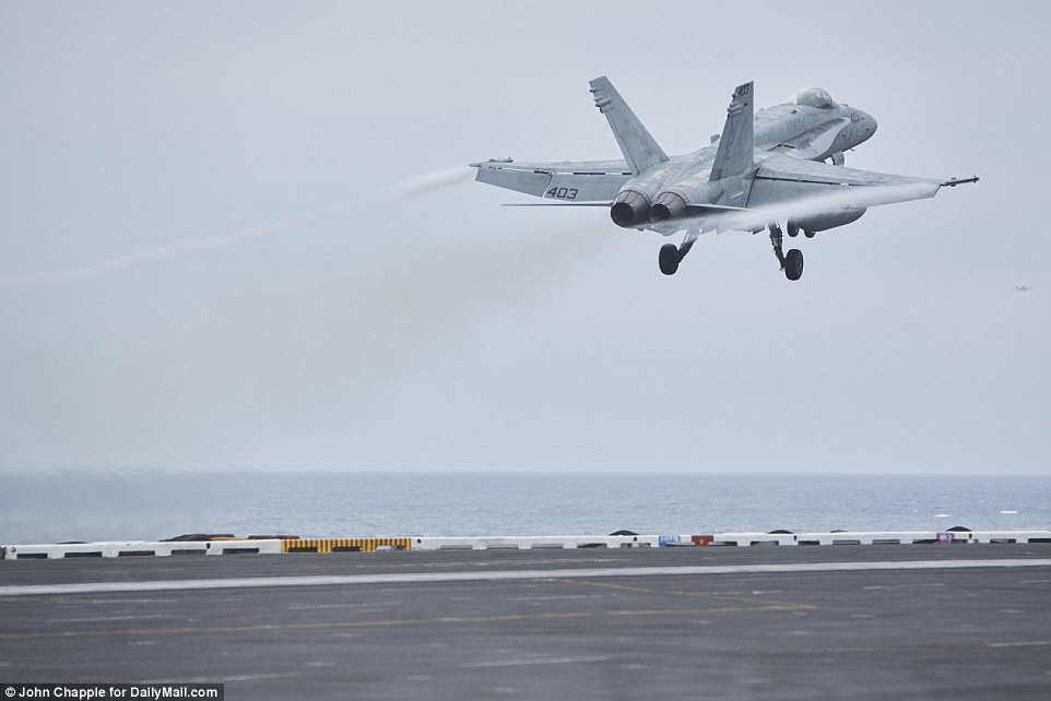 Aboard the 95,000 ton vessel, the twin engines of the F/A-18C Hornet were heard roaring off as the $70 million aircraft was catapulted off the deck. The strike fighter aircraft, which can reach Mach 1.8 (1,190mph), disappeared off the bow of the super carrier in a haze of steam