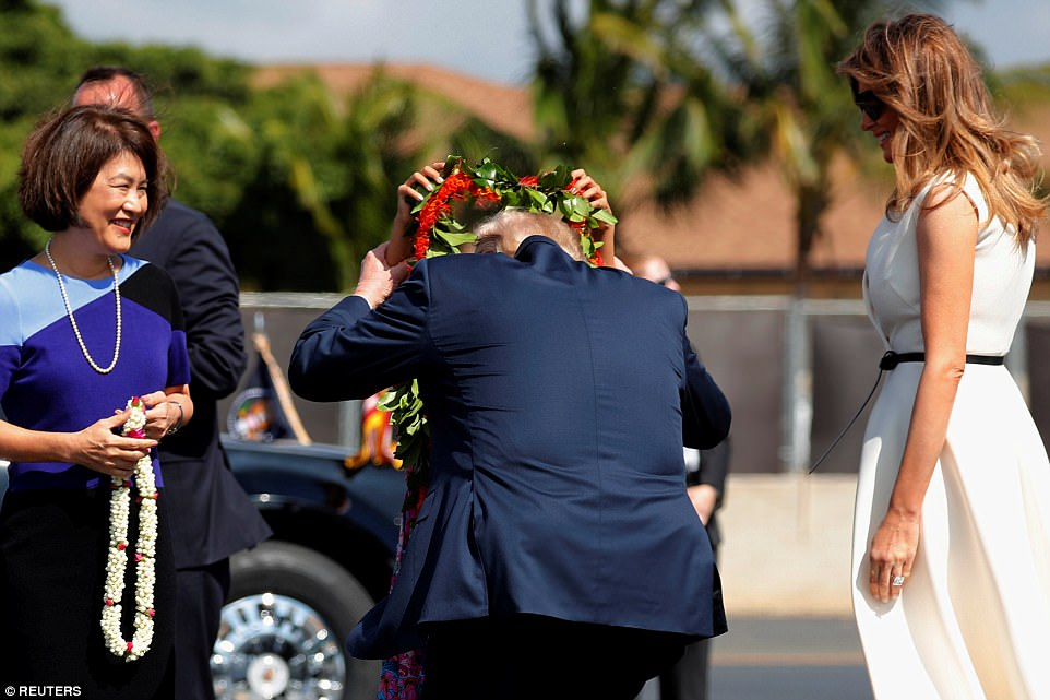 President Donald Trump bends to receive a flower lei as First Lady Melania Trump (far right) and Dawn Ige, the wife of Hawaii's governor, David Ige, look on