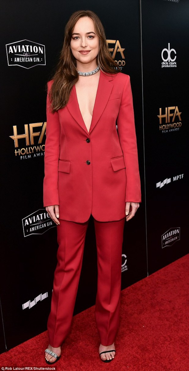 Stylish: Dakota Johnson showed up in a red pantsuit and went bra-less under the tailored jacket revealing cleavage. She wore a pair of sandal heels and a chunky necklace
