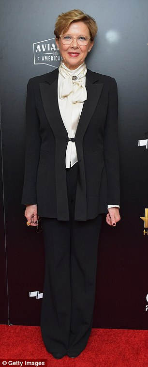 Veteran star Annette Bening, 59, wore wide-legged black slacks with a long black jacket fastened with a clip, She added a cream blouse with a bow and clasp at the neck