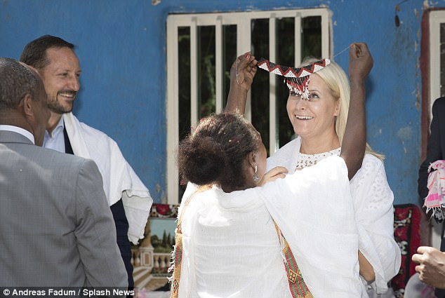 With her husband looking on, Mette-Marit prepared to have the band placed over her head