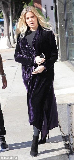 Mostrando su estilo: el abrigo largo y brillante terminaba justo debajo de sus rodillas mientras lo usaba sobre todo negro, incluida la parte superior, las polainas y los botines de gamuza.