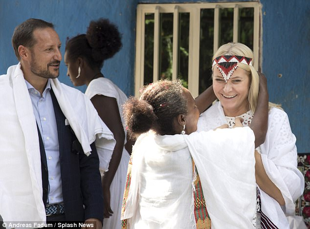 Charming: The princess beams as she is given a traditional beaded headband while her husband, Crown Prince Haakon, left, looks on
