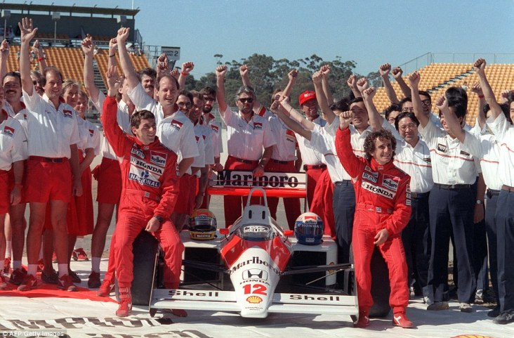 Senna and Prost pose with the almost unbeatable McLaren MP4/4 as well as McLaren and Honda personnel. The car won 15 of the year's 16 races - only losing in Monza due to a Prost engine failure and an infamous Senna crash. Prost outscored Senna by 11 points but fell victim to the rule that only a driver's best 11 results counted towards the drivers' championship standings