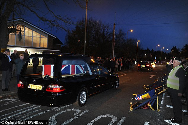 A hearse bearing the coffin of James Holloway makes its way through the streets of Headington in Oxfordshire