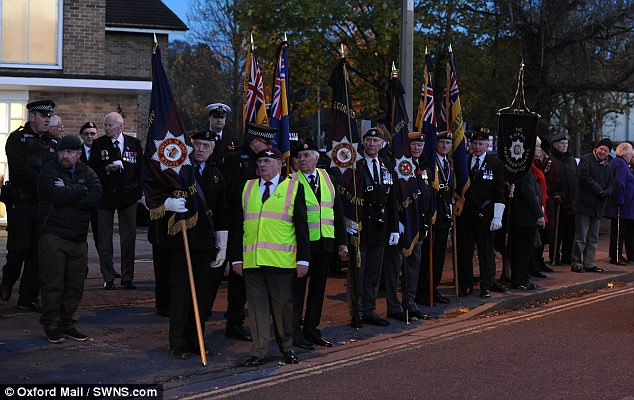 Standard bearers and armed forces veterans line the streets in Headington