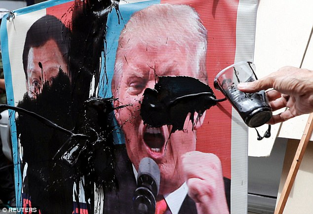 Protesters smear images of U.S. President Donald Trump and Philippine President Rodrigo Duterte with paint during a rally against US President's visit