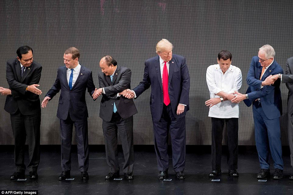 HOW DOES THIS WORK? U.S. President Donald Trump quizzically looked at his peers from Asian nations on Monday in the Philippines as they tried to execute the Association of South East Asian Nations traditional cross-armed handshake