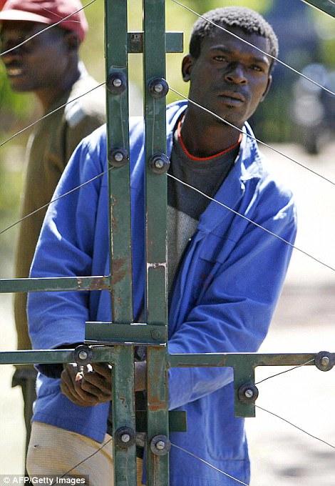Dos hombres de pie junto a las puertas de una granja que confiscaron a los granjeros blancos en 2009