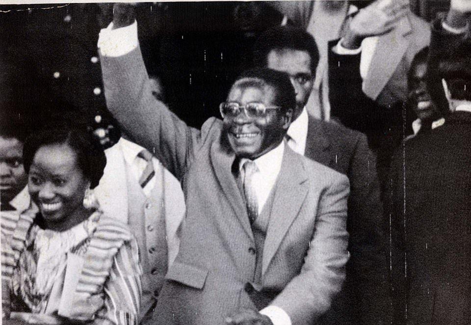 El primer ministro de Zimbabue, Robert Mugabe, da un triunfante saludo al salir del Parlamento tras su inauguración oficial el miércoles. A su derecha está su esposa, Sally