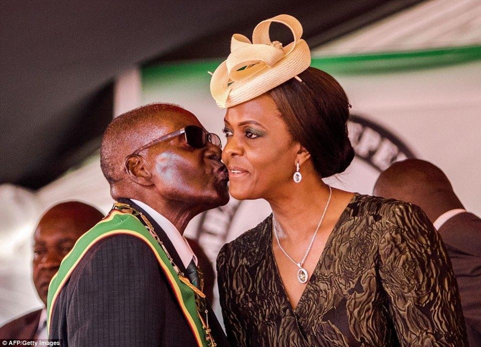 Esta foto de archivo tomada el 18 de abril de 2017 muestra al presidente Robert Mugabe besando a su esposa y a la primera dama Grace Mugabe durante las celebraciones del 37º Día de la Independencia del país en el Estadio Nacional de Deportes en Harare.