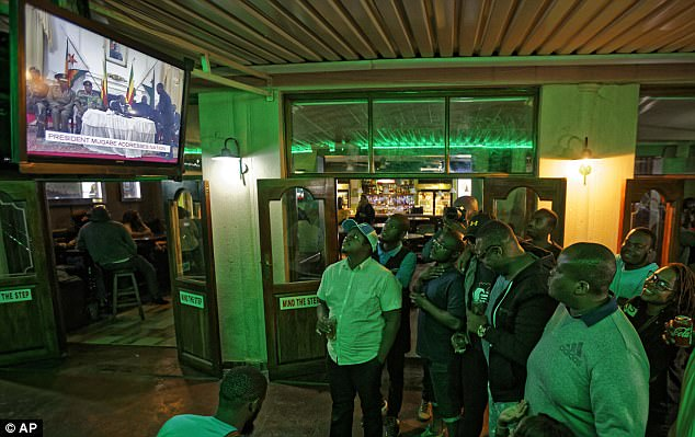 Men in a bar in Harare watch as Mugabe delivers a bizarre, rambling speech in which he failed to loosen his grip on power