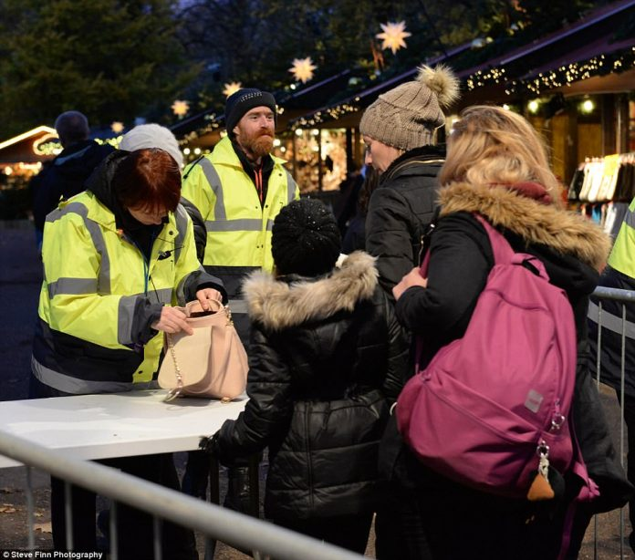 Rucksacks and women's handbags are searched at the entrance of London's popular Winter Wonderland festive market
