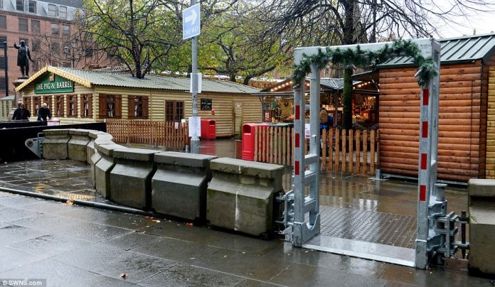 A metal gate is connected by a wall of concrete barriers outside Manchester's Christmas market as part of new strict security measures