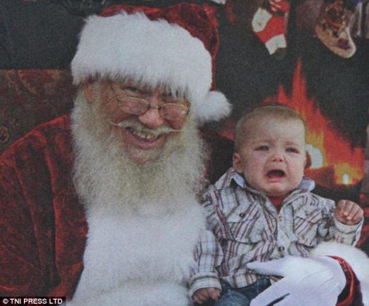 ¡Sólo sigue sonriendo!  Este Santa Claus no permite que las lágrimas de un niño se interpongan en una buena foto