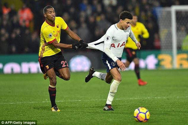 Tottenham midfielder Dele Alli (right) is pulled back by Watford's Marvin Zeegelaar