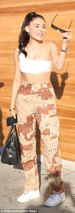 Double take:The 18-year-old songstress was wearing a very similar outfit to the bra-top, camouflage pants, and white Nike sneakers she donned at WeHo hotspot Delilah last Friday