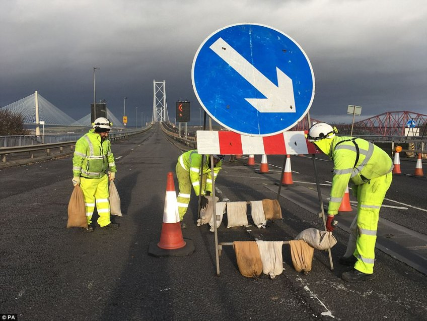 Workers on the Forth Bridge putting sandbags on a road sign to weigh down as forecasters warn of strong winds