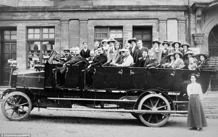 More than 25 people pose for a photograph while sat in a mass-person vehicle. On the side of the car, it is specified that the max speed of the vehicle is 12mph