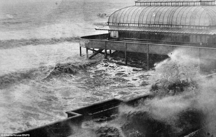 Rough seas are shown lapping onto the seafront in Burnham-on-Sea, Somerset. In 1911, a concrete wall was built along the seafront, and after the Second World War further additions  were made using the remains of a Mulberry harbour