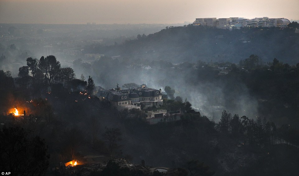 On Wednesday the newest wildfire, the Skirball Fire, set light to LA's plush Bel Air neighborhood (pictured). The Getty Center for the arts (top-right) was untouched by the fire, which failed to cross the dividing 405 highway