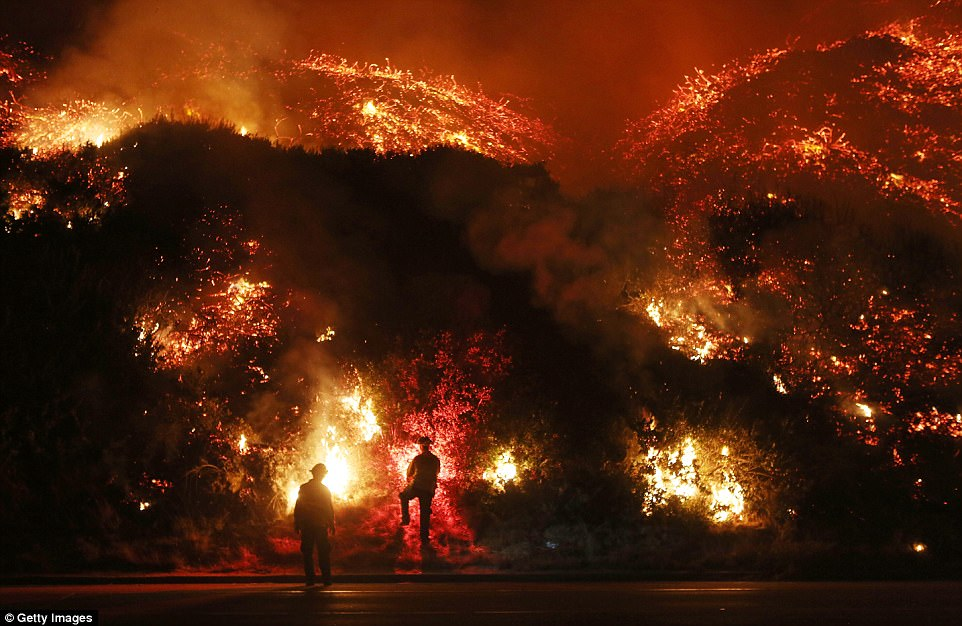 Firefighters monitor the Thomas Fire along Ventura's 101 freeway, using flares to burn off brush close to the road. Around 200,000 people are under evacuation orders across the state, and almost 200 homes and buildings have been destroyed
