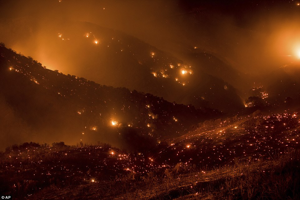 A hillside glows with embers as the Thomas fire burns through Los Padres National Forest near Ojai, California on Friday night