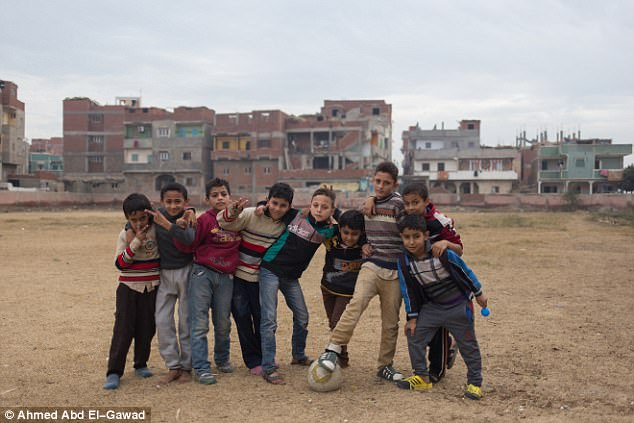 Nine young children play football on a dusty pitch in Salah's place of birth, Nagrig